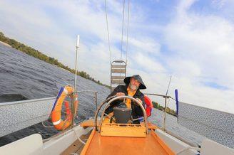Шкипер у штурвала на парусной яхты Благодать